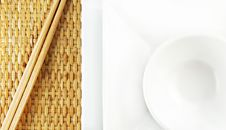 White Plates And Chopsticks On A Bamboo Mat Royalty Free Stock Images
