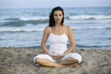Woman Making Yoga Exercise On The Beach Stock Image