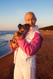Young Beautiful Woman With Her Dog On A Beach Stock Photo