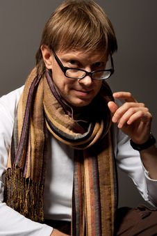 Man With Scarf Touching Glasses Royalty Free Stock Images