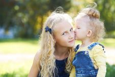 Sisters. Relations. Daughters. Portrait Children. Kiss. Love Stock Images