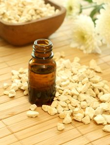 Bottle Of Essence Oil With Flowers And Stones Royalty Free Stock Photos