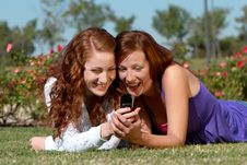 Two Girlfriends With A Mobile Phone In Park Royalty Free Stock Photos
