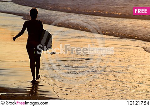 Silhouette of woman walking by the seaside Stock Photo