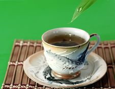 A Cup Of Green Tea And A Drop Of Water Stock Images