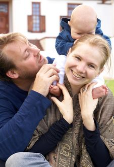 Happy Family Sitting On The Grass Royalty Free Stock Photos