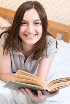 Free Smiling Student  Reads A Book Stock Images - 10187284