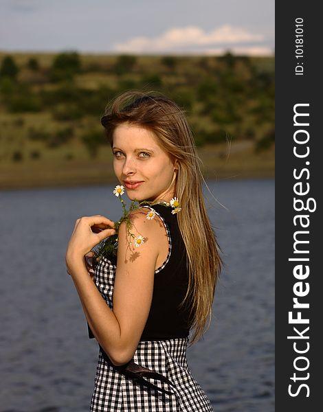 Nice girl on the lake coast with camomiles