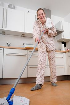 Woman In Pajamas Cleaning The Kitchen Royalty Free Stock Photography