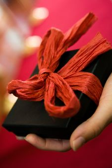 Hand Holding Gift With Red Bow Royalty Free Stock Photos