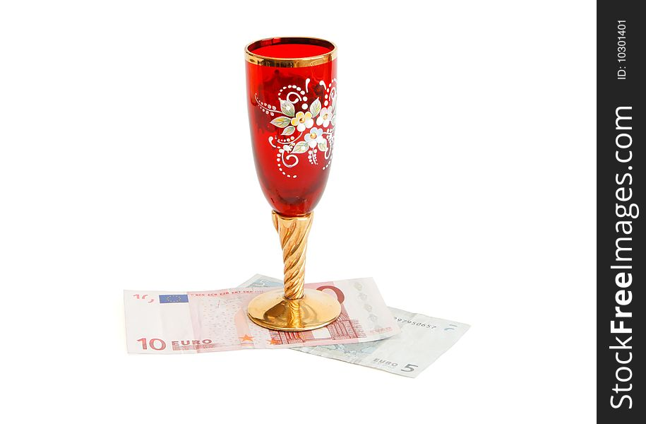 Beautiful wine glass on euro bills isolated