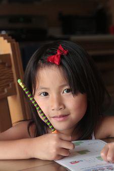 Free Smiling Asian Girl Doing Homework Stock Images - 10335714