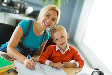 Cute Boy And His Mom Sit At The Desk In The Office And Draw Stock Photography