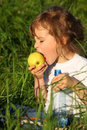 Free Girl With Plastic Bottle Eats Green Apple Royalty Free Stock Images - 10354859