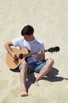 Free Guy Plays Guitar Sitting On Sand Stock Images - 10354384