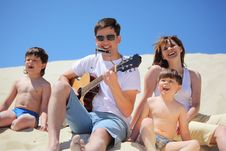 Guy Plays Guitar And Lip Accordion With Children Stock Photo