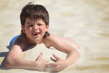 Free Boy Without  Foreteeth Lies On Sand Stock Photos - 10354533