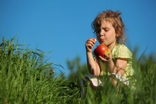 Free Girl Eats Red Apple In Grass Against Blue Sky Royalty Free Stock Image - 10354676