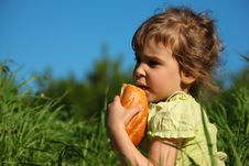 Free Girl Eats Bread In Grass Against Blue Sky Royalty Free Stock Photos - 10354718