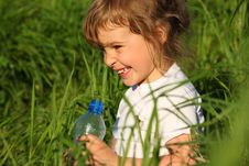 Smiling Girl In Grass With Plastic Bottle Royalty Free Stock Images