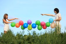 Girl And Guy Hold Garland Of Balloons