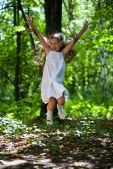 Girl Joyfully Jumps In The Wood Royalty Free Stock Image