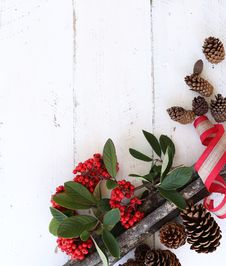 Free Red Fruits And Brown Pine Cones On White Wooden Surface Stock Photos - 103823243
