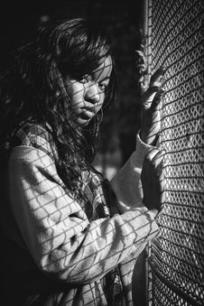 Free Grey Scale Photography Of Woman Standing Against Mesh Grill Stock Photography - 103898402