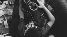 Free Man Playing Guitar Lying On Couch In Grayscale Photography Stock Photography - 104286982