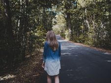 Free Woman Wearing Blue And White Long-sleeved Shirt Walking Near Tree Royalty Free Stock Photo - 104512845