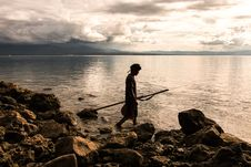 Free Person Holding Spear Beside Body Of Water Royalty Free Stock Photography - 104569917