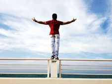 Free Person Raising Hands Mid-air Sidewards While Standing On Gray Steel Railings Stock Photos - 104635723