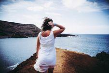 Free Woman Wearing White Sleeveless Mini Dress On Top Of Brown Sand Near Body Of Water Stock Image - 104712641