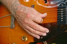 Aged Hand Playing Guitar Royalty Free Stock Image