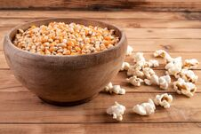 Raw Corn Seeds In Wooden Bowl And Popped Popcorn On Table Royalty Free Stock Image