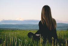 Free Woman Wearing Black Long Sleeved Shirt Sitting On Green Grass Field Near Mountain Under Cloudy Sky Stock Photography - 105662132