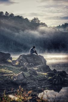 Free Man In Gray Shit Sitting On Rock Boulder Stock Photo - 105662400