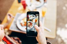 Free Person Holding Phone Taking Picture Of Served Food Stock Image - 105662591