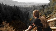 Free Man In Black Shirt And Brown Backpack Leaning On Brown Wooden Handrail Looking Over Green Leaf Pine Trees And Creek Stock Photography - 105741752