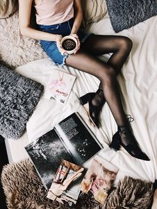 Free Flatlay Photography Of A Woman Holding White Mug With Black Liquid While Lying On A Bed Surrounded By Fur Pillows And Magazines Stock Image - 105741901