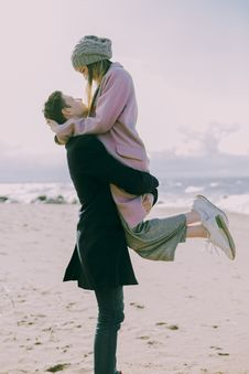 Free Man In Gray Coat Carrying Woman Wearing Pink Coat In Beach Near Shoreline And Body Of Water Stock Photos - 105823733