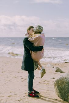 Free Man In Black Overcoat And Blue Denim Jeans Kissing While Carrying A Woman In Pink Overcoat And Knit Cap On Shore At Daytime Royalty Free Stock Photos - 105823748