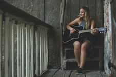 Free Woman Wearing Gray Tank Top Playing Black Cutaway Acoustic Guitar Stock Image - 105911811