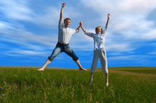 Free Jumping Couple In Field Under Clouds Stock Photography - 1061002