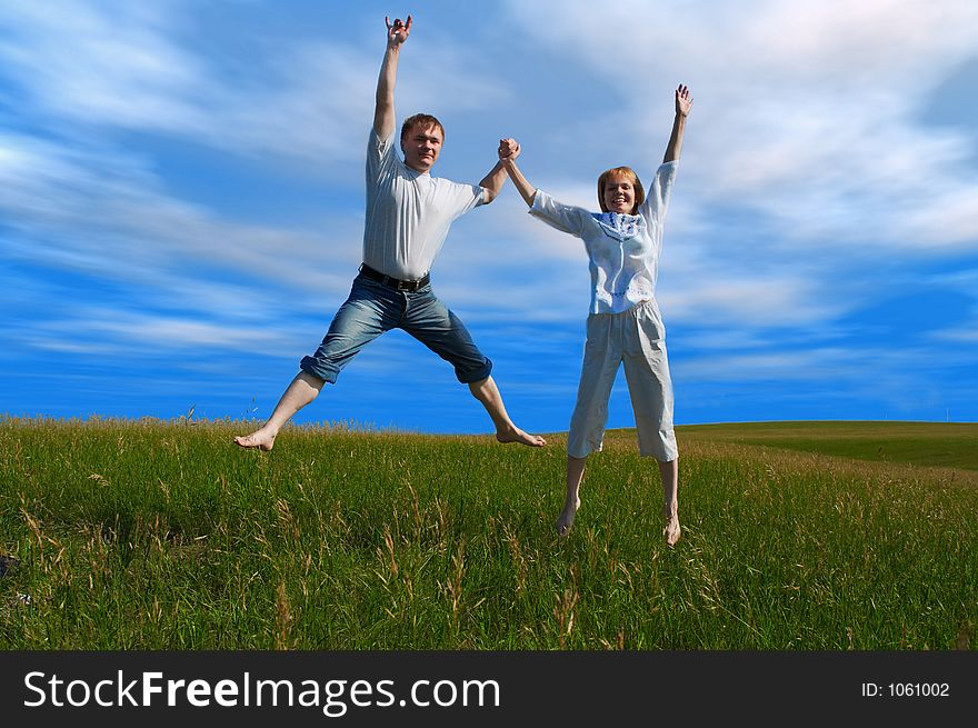 Jumping couple in field under clouds
