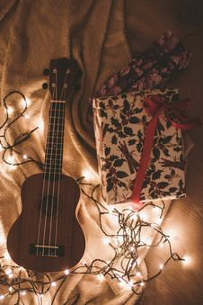 Free Ukulele Beside A Floral Box And String Lights Royalty Free Stock Photos - 106058478