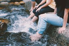 Free People In Jeans With Feet In Water Royalty Free Stock Photography - 106123377