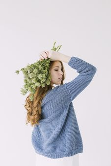 Free Woman In Blue Knit Cable Sweater Holding Green Petaled Flowers Stock Images - 106174154
