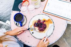 Free Woman Holding Spoon And Fork With Blackberries On Plate Beside Blue Ceramic Mug On White Wooden Table Stock Photography - 106174272