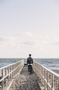 Free Man In Black Jacket Walking On Gray Concrete Dock Royalty Free Stock Images - 106174369